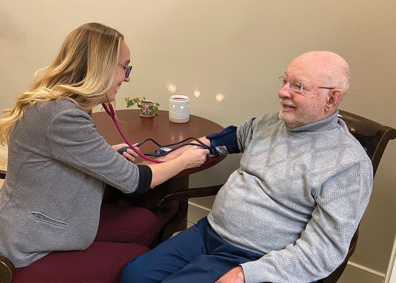 nurse taking blood pressure of gentleman